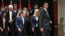 Prime Minister Justin Trudeau, right, is seen with his cabinet in Calgary, on Tuesday. The results from the survey, are likely to add even more uncertainty to Prime Minister Justin Trudeau's 2015 campaign promise to change the first-past-the-post voting system before the next election.<252> (Jeff McIntosh/THE CANADIAN PRESS)