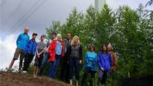 Anmore residents, who are concerned about a BC Hydro power line expansion near their homes, pose in front of one of the existing towers. (Lynn Burton)