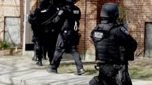 Officers in tactical gear enter an apartment building in Watertown, Mass., on Friday, April 19, 2013. (Julio Cortez/Associated Press)