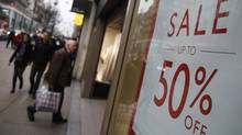 Shopper pass a sale sign on Oxford Street in London. (© Neil Hall / Reuters)
