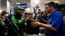 "Gaming fan Jim Cush (L), dressed as the character Master Chief from the Xbox 360 video game ""Halo 3"", purchases his copy of the game during a midnight sales event in New York."