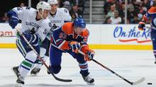 Ryan Nugent-Hopkins of the Edmonton Oilers gets around Aaron Volpatti of the Vancouver Canucks during second-period action in a preseason game Thursday, Sept. 22 at Rexall Place in Edmonton,. (Dale MacMillan/Getty Images)