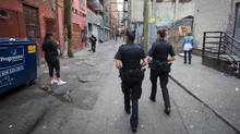 Vancouver Police officers, Cnst. Jennifer Antonel, centre, and Cnst. Courtney Park, right, walk through an alley behind East Hastings Street while working in the Downtown Eastside of Vancouver, B.C., on Monday July 11, 2016. (DARRYL DYCK For The Globe and Mail)