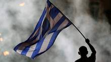 A supporter of the New Democracy party waves a Greek flag during an election rally at Syntagma square in Athens, Friday, June 15. (Petros Karadjias/AP)