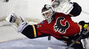 Calgary Flames goalie Miikka Kiprusoff, from Finland, dives on the puck during second period NHL action against the Columbus Blue Jackets in Calgary, Alta., on Friday, March 29, 2013.