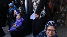 Palestinian women wait to register their names to obtain a travelling date, in Gaza City October 20, 2013. Egyptian authorities partially opened Rafah Crossing, Gaza's main window to the world, on Sunday for six days for humanitarian cases and stranded students, but the crossing, according to local media, is experiencing slow passage. (MOHAMMED SALEM/REUTERS)