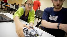 Duru Uluk, 13 and a Grade 8 student, attends a weekly after-school program at the University of Waterloo for elementary and secondary students to build and program computerized Lego robots. She tests her robotic vehicle with program supervisor Martin Scherer, right. (Glenn Lowson for The Globe and Mail)