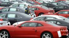 A worker is shown in a sea of new cars at a storage lot adjacent to the General Motors assembly plant offices in Oshawa, Ont., in this file photo. (Kevin Van Paassen/THE GLOBE AND MAIL)