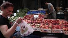 A woman buys peaches from a fruit vendor at a grocery market in Athens on Aug. 8, 2014. (ALKIS KONSTANTINIDIS/REUTERS)