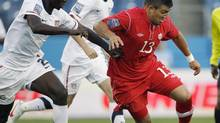 Lucas Cavallini (13), of Canada, dribbles the ball as he is defended by Ike Opara (2) and Mix Diskerud, center, of the United States, in the first half of a CONCACAF Olympic qualifying soccer match on Saturday, March 24, 2012, in Nashville, Tenn. (Mark Humphrey/The Associated Press)