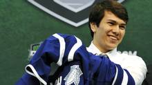 Stuart Percy puts on a jersey after being drafted in the first round by the Toronto Maple Leafs in the National Hockey League entry draft, Friday, June 24, 2011, in St. Paul, Minn. (Jim Mone/Associated Press)
