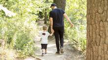 Kevin Naulls walks with his partner's adopted son, Junior. For a time, he had to be a silent partner in the relationship, but now helps parenting. (Jenna Marie Wakani/the globe and mail)