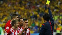 Referee Yuichi Nishimura of Japan shows the yellow card to Croatia's Dejan Lovren for a foul on Brazil's Fred (unseen), during the 2014 World Cup opening match at the Corinthians arena in Sao Paulo June 12, 2014. (Reuters)