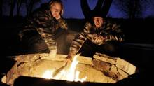 A couple warms themselves by a campfire in Colorado Springs, Colo. on Jan. 21, 2010. A sobering reminder of the fatal potential of burns came earlier this month when a 53-year-old woman died after falling into a firepit at a private campsite in central Alberta. (Craig F. Walker/THE CANADIAN PRESS)