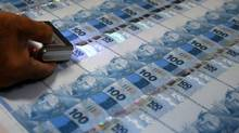 A worker checks currency sheets at the Casa da Moeda do Brazil (Brazilian Mint) in Rio de Janeiro. (SERGIO MORAES/REUTERS)