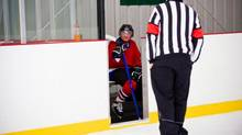 Referee puts hockey player in penalty box (Photos.com)