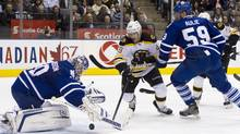 Toronto Maple Leafs goaltender Jonas Gustavsson (left) drops onto the puck in front of Boston Bruins Rich Peverley (centre)as Leafs' Keith Aule looks on during first period NHL hockey action in Toronto on Wednesday November 30, 2011. (Chris Young/THE CANADIAN PRESS)