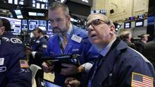 Traders Kevin Lodewick, left, and Richard Cohen work on the floor of the New York Stock Exchange, Monday, Sept. 26. (Richard Drew/AP)