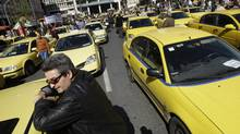 Taxi drivers demonstrate outside the Greek Finance Ministry during their 48-hours strike in Athens on Tuesday. (Petros Giannakouris/AP2010)