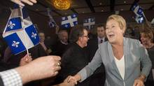 Parti Quebecois leader Pauline Marois greets supporters as she arrives at a general council meeting in Laval, Que., Saturday, March 8, 2014 on day four of the Quebec provincial election campaign. (Graham Hughes/THE CANADIAN PRESS)
