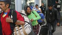 Romanian Roma people carry luggage after they and more than 200 others arrived on two special flights from France, in Bucharest, Romania, Tuesday, Sept. 14, 2010. (Vadim Ghirda/AP)