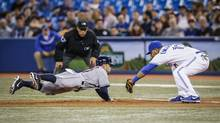 The Toronto Blue Jays' Edwin Encarnacion tags the Houston Astros' Jose Altuve on a pickoff by R.A. Dickey during the fourth inning in Toronto on Thursday, April 10, 2014. (Mark Blinch for The Globe and Mail)