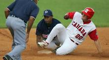 Canada's Michael Saunders, right, is tagged out in the second base by Dominican Republic's Hilario De La Cruz in the third inning during their Olympic qualifying baseball game at Nelson Fernandez stadium in San Jose de Las Lajas just outside of Havana, Cuba, Sunday, Sept. 3, 2006. (FERNANDO LLANO/AP)