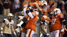 B.C. Lions' Ben Archibald, 65, lifts quarterback Travis Lulay, 14, after Lulay scored a touchdown as teammate Jon Hameister-Ries, 67, joins in the celebration while Winnipeg Blue Bombers' Pierre-Luc Labbe, left, walks away during the second half of a CFL football game in Vancouver, B.C., on Friday June 29, 2012. (The Canadian Press)