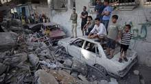 Palestinians look the damage of a destroyed house where five members of the Ghannam family were killed in an Israeli missile strike early morning in Rafah refugee camp, southern Gaza Strip on Friday, July 11, 2014. (Khalil Hamra/Associated Press)