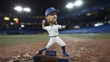 The Blue Jays will be giving away R. A. Dickey bobbleheads to the first 20,000 fans this Sunday. The smaller version warmed up on the Rogers Centre pitching mound on Thursday. (Fred Lum/The Globe and Mail)
