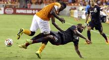 Toronto FC's Jermain Defoe (18) falls to the ground as he is hit by Houston Dynamo's Warren Creavalle, left, during the second half of a MLS soccer game Saturday, July 19, 2014, in Houston. Toronto FC and the Houston Dynamo played to a 2-2 tie. (David J. Phillip/AP)