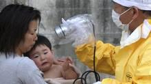 A one-year-old boy is re-checked for radiation exposure after being decontaminated in Nihonmatsu, Fukushiima, northern Japan Monday, March 14, 2011. (Toru Nakata/Asahi Shimbun, Toru Nakata/AP)
