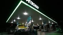 Motorists pump fuel at a Petronas station in Putrajaya, Malaysia. (BAZUKI MUHAMMAD/REUTERS)
