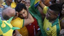 A Brazilian fan, left, consoles a Chilean fan after Brazil defeated Chile on a World Cup round of 16 soccer match in Belo Horizonte, Brazil, Saturday, June 28, 2014. (Victor R. Caivano/AP)