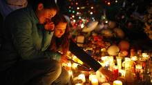 Girls light candles at a memorial set up to honour the victims of the shooting at Sandy Hook Elementary School in Sandy Hook Village in Newtown, Conn., December 18, 2012. (ERIC THAYER/REUTERS)