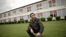 Bill Chu, chairman of Canadians for Reconciliation, kneels on the lawn of New Westminster Secondary School, where he says it is inappropriate for the school to rebuild on the site of what could be a historical Chinese cemetary. (Simon Hayter/SIMON HAYTER FOR THE GLOBE AND MAIL)