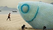 A man runs along the beach near a huge sculpture made from plastic bottles in Rio de Janeiro during the United Nations Conference on Sustainable Development on June 19, 2012. (Victor Caivano/Associated Press)