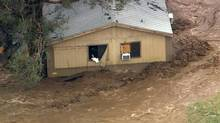 A man stands in the window of a flooded house in New River, Ariz., north of Phoenix, on Aug. 19, 2014. The area was flooded after several inches of rain pummelled the state. (ABC15 TV/ASSOCIATED PRESS)