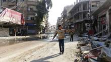 A boy gestures towards damaged buildings after what opposition activists said was shelling by forces loyal to Syria's President Bashar al-Assad at Daria near Damascus November 25, 2012. (Fadi al-Derani/Shaam News Network//REUTERS)