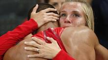 United States' Ashton Eaton is embraced by his fiancee Brianne Theisen after he won the decathlon during the athletics in the Olympic Stadium at the 2012 Summer Olympics, London, Thursday, Aug. 9, 2012. Theisen will marry Eaton on Saturday in Eugene, Ore., the latest chapter in an Olympic-sized love story that began when the two met as teenagers at the University of Oregon. (Matt Dunham/AP)