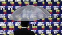 A pedestrian holding an umbrella looks at an electronic stock board outside a securities firm in Tokyo, Japan, on Wednesday, Sept. 9, 2015. (Kiyoshi Ota/Bloomberg)