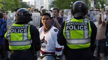 A Vancouver Canucks fan confronts the police during riots after the Canucks lost Game 7 of the NHL Stanley Cup final hockey game to the Boston Bruins in Vancouver, British Columbia June 15, 2011. (MIKE CARLSON/Mike Carlson/Reuters)