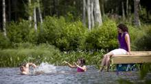 Melanie Taljaard, along with her son Jacob Taljaard and daughter Madison Tuljaard cool off in Miller Lake in Fall River, NS, on a hot summer day. (Sándor Fizli for The Globe and Mail)