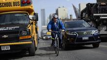 A cyclist heading westbound on Toronto's Bloor St. West manoeuvres between parked vehicles on the left and live traffic on the right on March 8, 2016. (Fred Lum/The Globe and Mail)