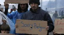 "A refugee holds a placard reading ""Sorry Belgium"" during a protest demanding the opening of the Greek-Macedonian border on March 23, 2016. (Alexandros Avramidis/Reuters) (ALEXANDROS AVRAMIDIS/REUTERS)"