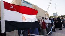 A national flag waves as Egyptians line up outside a polling station to cast their votes during the first day of the presidential elections in Alexandria, Egypt, Wednesday, May 23, 2012. (Khalil Hamra/Khalil Hamra/AP)