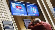 A trader reacts as he looks at computer screens at the Madrid Bourse July 24, 2012. Spain and Italy both introduced short-selling bans on Monday, reacting to steep falls in their stock markets and as confidence slipped in their ability to repay their debts, prop up their banking systems and tend to their economies while remaining within the euro currency. (ANDREA COMAS/REUTERS)