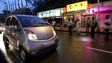 Pedestrians watch the first Tata Nano car being driven on the road in Mumbai, India, Friday, July 17, 2009. (Rajanish Kakade/AP)