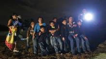 This June 25, 2014, photo shows a group of immigrants from Honduras and El Salvador who crossed the U.S.-Mexico border illegally as they are stopped in Granjeno, Texas. (Eric Gay/Associated Press)
