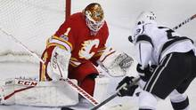 Calgary Flames goalie Brian Elliott, left, makes a save against Los Angeles Kings' Dustin Brown during second period NHL action in Calgary, Alta., Sunday, March 19, 2017. (Larry MacDougal/THE CANADIAN PRESS)